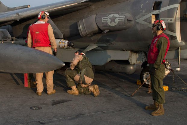 Marines, attached to the 26th Marine Expeditionary Unit (MEU), perform last minute checks of an AV-8B Harrier. Photo by Mass Communication Specialist Seaman Tyler Preston