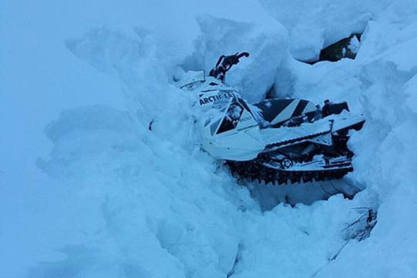 A snowmobile is buried in a snowbank after the operator becomes stranded near Dan Moeller Bowl on Douglas Island near Juneau, Alaska, Jan. 5, 2016.  (U.S. Coast Guard photo)