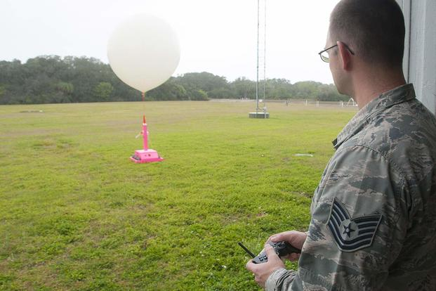 "Tech Sgt. Matthew Mong, a 45th Weather Squadron range weather forecaster, demonstrates how to use a ""weatherbot"" at the weather balloon facility on Cape Canaveral Air Force Station, Fla. (U.S. Air Force/Sean Kimmons)"