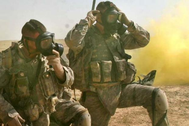 Soldiers don and clear their masks during training for a chemical attack. (Photo Credit: Marine Corps Sgt. Andrew D. Pendracki)