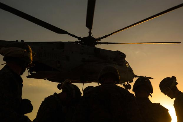 Marine Infantry Officer Course students await a CH-53E Super Stallion helicopter fast rope drill on the Marine Corps Air Station Yuma, Ariz., Auxiliary Landing Field 2, Wednesday, August 18, 2014. (U.S. Marine Corps/ Cpl. James Marchetti)