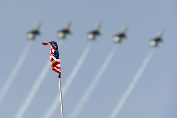 A gust of wind waves an American flag as the U.S. Air Force Air Demonstration Squadron, the Thunderbirds, perform at Osan Air Base. (U.S. Air Force photo/Staff Sgt. Brian Ferguson)