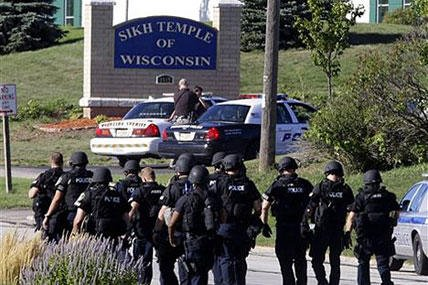 Police walk near the Sikh Temple of Wisconsin in Oak Creek, Wis., after a shooting Sunday. A gunman killed six people at the suburban Milwaukee temple in a rampage that left terrified congregants hiding in closets and others texting friends.