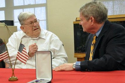 World War II veteran Charles Bledsoe, 88, left, talks with U.S. Sen. Tim Johnson, D-S.D., Wednesday, May 1, 2013, as he's awarded a Purple Heart and Bronze Star for injuries sustained in combat at the Veterans Administration hospital in Sioux Falls, S.D.