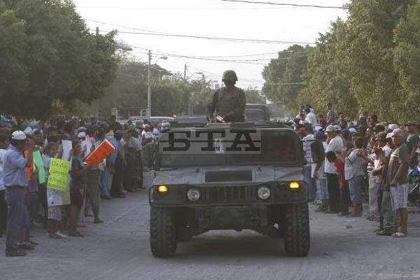 Residents of La Ruana, Michoacan, Mexico,greet Mexican army soldiers arriving to support the town's militia against a drug cartel on May 20, 2013. AP Photo/Marco Ugarte