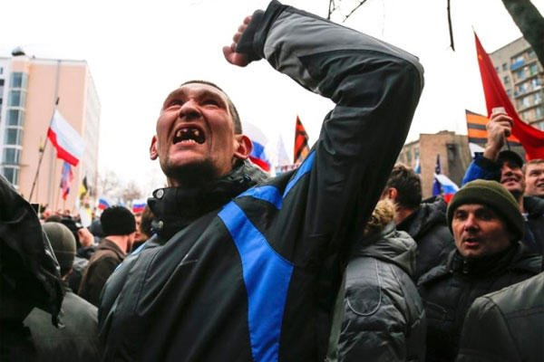 A pro-Russia demonstrator gestures as others storm the prosecutor-general's office during a rally in Donetsk, Ukraine, Sunday, March 16, 2014.