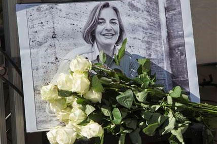 In this Saturday, April 5, 2014 file photo, roses lay in front of a picture of the Associated Press photographer Anja Niedringhaus, 48, who was killed April 4, 2014 in Afghanistan, in Paris.
