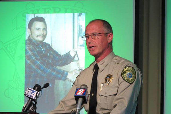 Storey County Sheriff Gerald Antinoro speaks to reporters in Reno, Nev., Thursday, May 1, 2014, about the opening of an investigation into the apparent 1980 homicide of George Benson Webster, who is pictured in the background. (AP Photo/Scott Sonner)