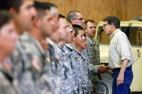 Gov. Rick Perry shakes hands with National Guard troops training at Camp Swift on Aug. 13 in Bastrop, Texas. (William Luther / AP)