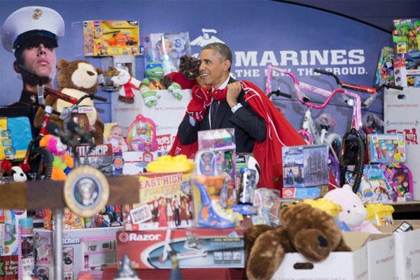 President Barack Obama carries two bags of gifts as he arrives to help first lady Michelle Obama sort toys and gifts for the Marine Corps' Toys for Tots Campaign, Wednesday, Dec. 10, 2014, at Joint Base Anacostia-Bolling. PABLO MARTINEZ MONSIVAIS/AP
