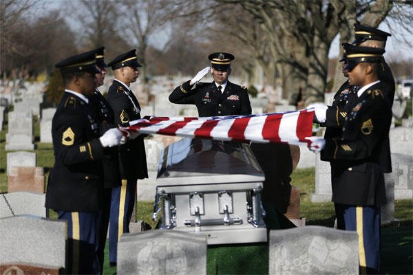 A soldier salutes during a graveside service for Anthony La Rossa in Farmingdale, N.Y., Monday, Dec. 15, 2014. (AP Photo/Seth Wenig)