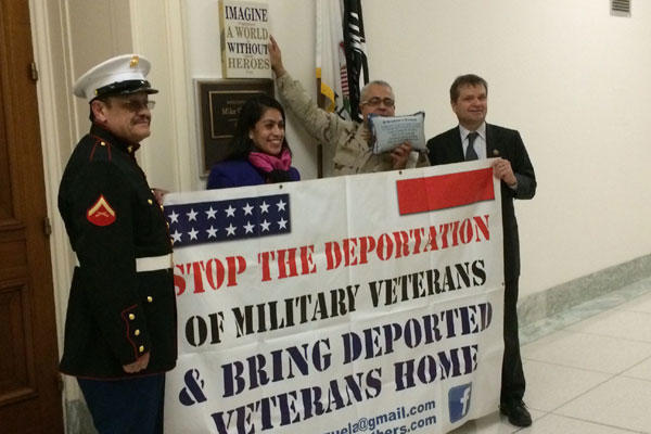 Marine Vietnam veteran Manuel Valenzuela holds up protest banner with, from left, Susana Sandoval of Dream Moms USA, former Petty  Officer 3rd Class Esteban Burgoa and Rep. Mike Quigley, D-Illinois, outside Quigley's office on Jan. 6.
