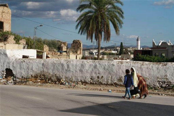 In this Dec. 5, 2014 photo, people walk in the low-income Tunis suburb of Mhamdiya, Tunisia, which has produced a number of young men that left to fight in Syria for extremist groups. (PAUL SCHEMM/AP)