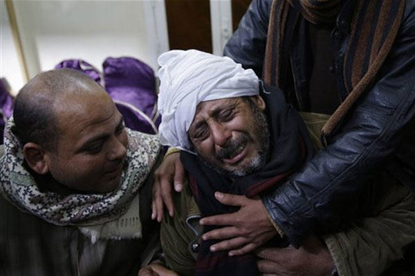 A man is comforted by others as he mourns over Egyptian Coptic Christians who were captured in Libya and killed by militants affiliated with the Islamic State group, in the village of el-Aour, near Minya, Feb. 16, 2015. (HASSAN AMMAR/AP Photo)