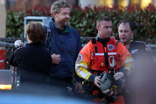 Louis Jordan, second from left, walks from the Coast Guard helicopter to the Sentara Norfolk General Hospital in Norfolk, Va., after being found off the North Carolina coast, Thursday, April 2, 2015. (AP Photo/The Virginian-Pilot, Steve Earley)