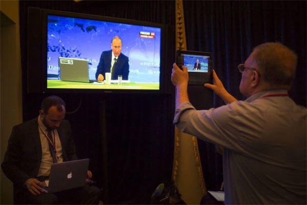 A journalist takes a picture from a TV screen while Russian President Vladimir Putin speaks during a nationally televised question-and-answer session in Moscow in Moscow, Russia, Thursday, April 16, 2015. (Alexander Zemlianichenko/Associated Press)