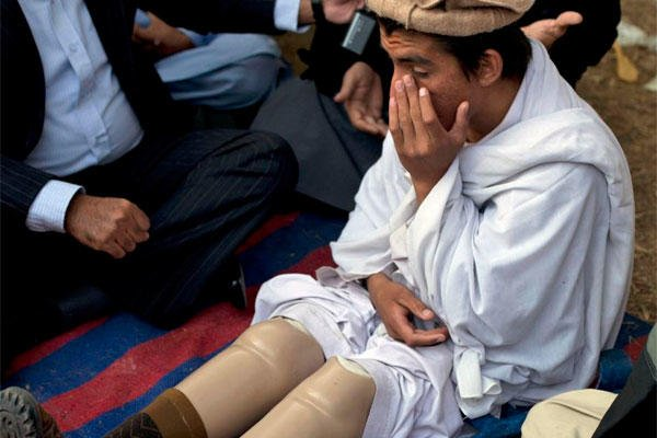 In this Dec. 10, 2010, file photo, Pakistani tribal youth Saadullah Wazir, who reportedly lost his legs in a drone attack, sits during a protest in Islamabad, Pakistan. (AP Photo/B.K. Bangash, File)
