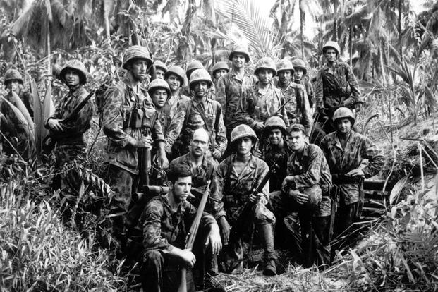 This January, 1944, file photo shows U.S. Marine Raiders posing in front of a Japanese stronghold they conquered at Cape Totkina, Bougainville in the Solomon Islands. (AP Photo/File)
