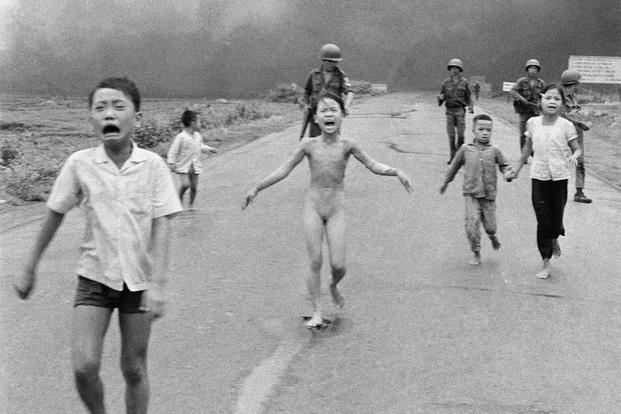 "In this June 8, 1972, file photo taken by Huynh Cong ""Nick"" Ut, South Vietnamese forces follow behind terrified children, including 9-year-old Kim Phuc, center, as they run down Route 1 near Trang Bang after an aerial napalm attack. (AP Photo/Nick Ut)"