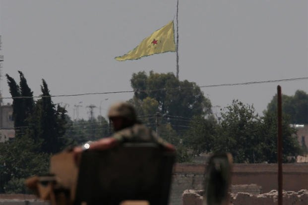 In this photo taken from the Turkish side of the border between Turkey and Syria, a Turkish soldier watches as a flag of the Kurdish People's Protection Units, is raised over the city of Tal Abyad, June 16, 2015. (AP Photo/Lefteris Pitarakis)