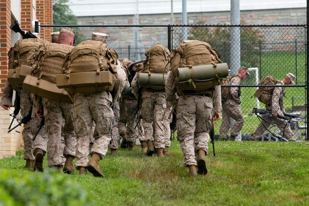 Troops move carrying guns walk at the Navy Yard in Washington, Thursday, July 2, 2015. A lockdown is underway on the entire Washington Navy Yard campus after a report of shots fired. (AP Photo/Jacquelyn Martin)