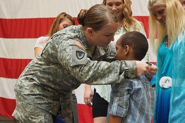 New York Army National Guard Staff Sgt. Marlana Watson presents her New York State Medal for Valor, to her son, Lassan Green.(U.S. Army/Sgt. J.P. Lawrence)