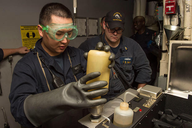 Engineman 2nd Class Changxuan Zhou, left, receives training from Chief Engineman Robert Carter on the combined contaminated fuel detector. (U.S. Navy photo by Mass Communication Specialist 2nd Class Joe Bishop)