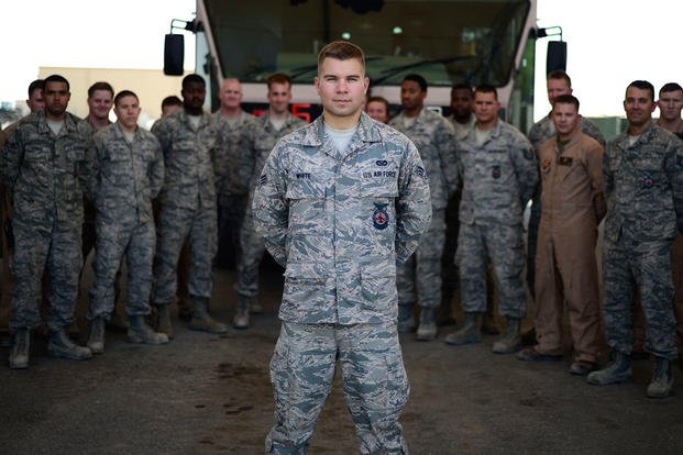 Senior Airman Zach White, a 332nd Expeditionary Civil Engineer Squadron firetruck operator and truck engineer, stands in front of his firefighter comrades in Southwest Asia, Aug. 20, 2015. (U.S. Air Force photo/Senior Airman Racheal E. Watson)