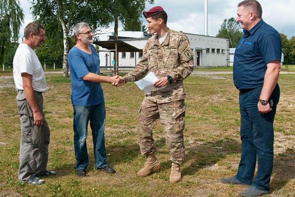 U.S. Army Pfc. Aidarbek Raev talks with military contractors about a construction project in Lithuania. Raev, a native of Bishkek, Kyrgyzstan, is fluent in Russian, the second-most common language in Lithuania. (U.S. Army/Sgt. Jarred Woods)