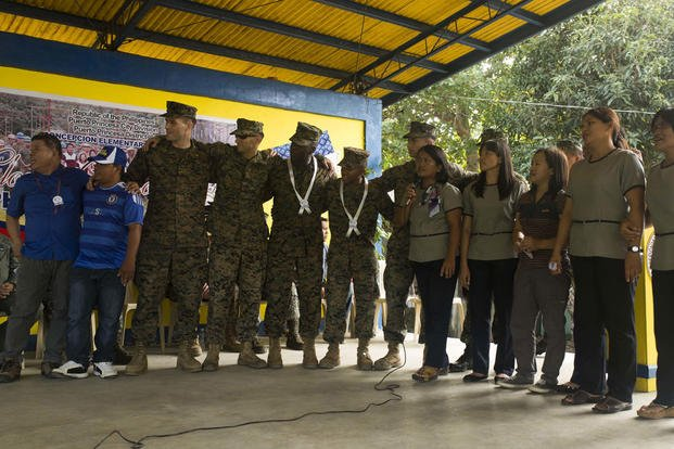 Marines and the teachers and staff of Concepcion Elementary School sing together during an intermission at the ribbon cutting ceremony Oct. 8, during Amphibious Landing Exercise 2015. (Photo By: Lance Cpl. Robert D. Williams Jr)