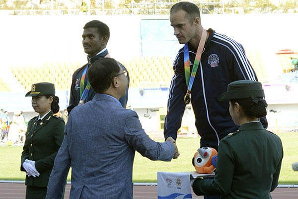 U.S. Army Sgt. Robert Brown shakes hands with Korean Track and Field Association Vice President Hwang Gu Hoon after receiving the gold medal for the 100-meter para dash at the CISM in Mungyeong, South Korea, Oct. 5, 2015. (U.S. Army/ Gary Sheftick)
