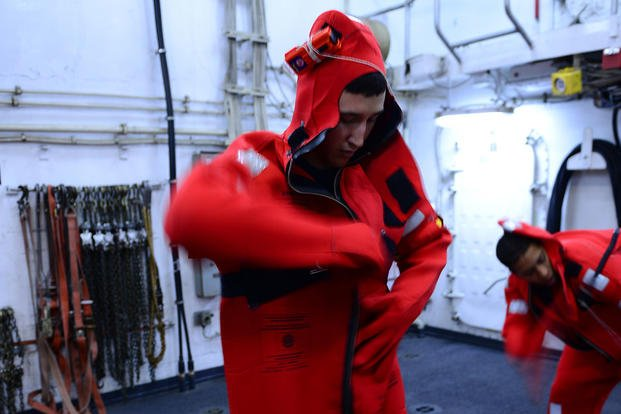 Seaman Cody DeGracia puts on an immersion suit during training aboard the Coast Guard Cutter Midgett while on a Living Marine Resources patrol off the coasts of Washington and Oregon Oct. 9, 2015. (Photo by Petty Officer 1st Class Levi Read)