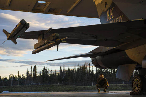 Senior Airman Terrence Lawrence, a 354th Aircraft Maintenance Squadron aircraft electrical and environmental systems journeyman, prepares an F-16 Fighting Falcon for a mission, Alaska, Oct. 8, 2015. (Photo: Staff Sgt. Joshua Turner)