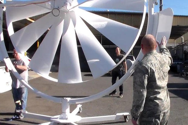Natural Power Concepts personnel and Lt. Col. Scott Fitzner, of the AFRL Materials and Manufacturing Directorate, inspect the spoke wheel medium wind power system. (Courtesy photo/Hawaii Center for Advanced Transportation Technologies)
