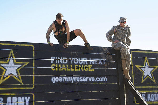 "A competitor at the 2015 Southern California Tough Mudder competition in Temecula, Calif., Oct. 31, 2015, attempts the ""Berlin Wall,"" one of the 21 obstacles in this year's event, flanked by Pfc. Dane E. Shoebotham. (U.S. Army photo)"
