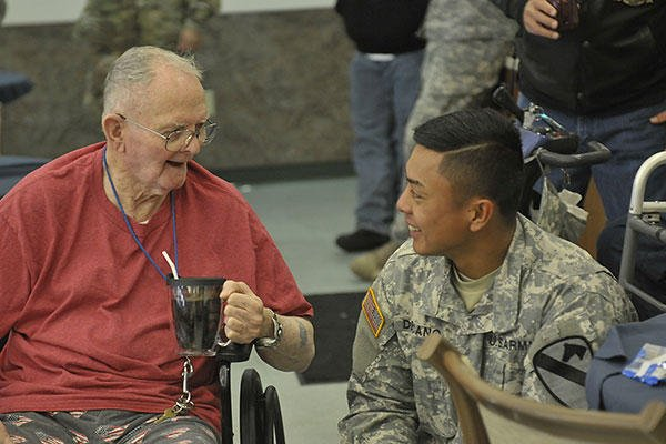 Sgt. Guian Decano, right, talks to a veteran, left, at the William R. Courtney Texas State Veterans Home in Temple, Texas, Dec. 18, 2015. (U.S. Army/Sgt. Brandon Banzhaf)