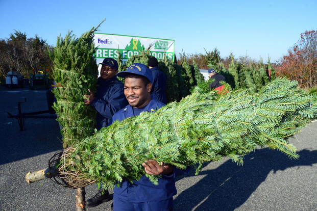 Petty Officer 2nd Class Raqueel Archibald carries the Christmas tree he selected during the Trees for Troops delivery, Friday, Dec. 4, 2015. (U.S. Coast Guard Photo by Chief Warrant Officer John Edwards)