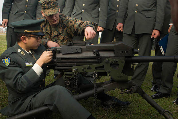 Pfc. Cooper Rottinghaus shows Japan Ground Self-Defense Force officer candidate Kazuhisa Takeda how to operate a MK19 machine gun, MOD 3 on Camp Kinser, Okinawa, Japan, Jan. 15. (Photo: Cpl. Robert D. Williams Jr.)
