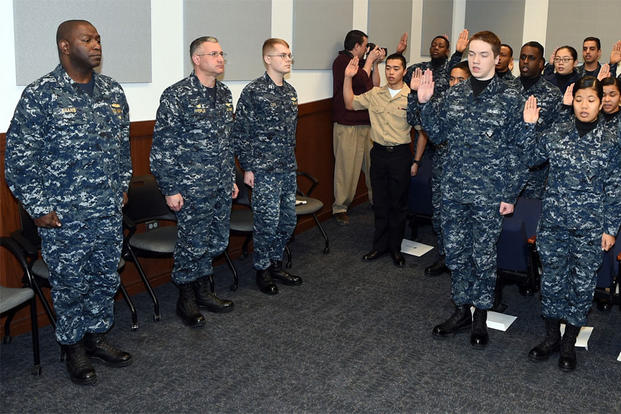Rear Adm. Stephen C. Evans (left), commander, NSTC, and Capt. W. David Pfeifle, commanding officer, Recruit Training Command (RTC), observe 18 recruits and Sailors take the Oath of Citizenship during a naturalization ceremony. (Photo: Scott A. Thornbloom)