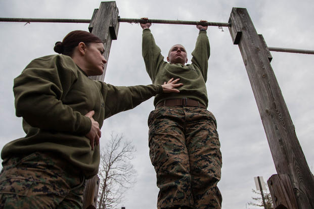 Major Misty Posey, left, assists a Marine doing pull-ups at Marine Corps Base Quantico, Virginia, Feb. 19, 2016. (Photo: Sgt. Dylan Bowyer)