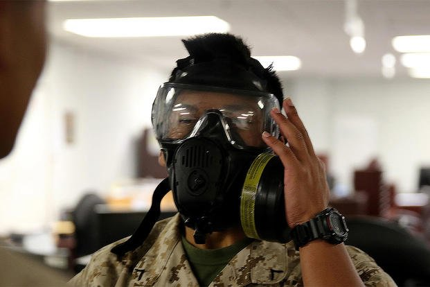 Pfc. Amethyst Bou with H&S company for Chemical Biological Incident Response Force, CBIRF, Marine Corps Forces Command inspects his M53 gas mask for a proper seal, during gas mask drills on June 7. (Photo: Lance Cpl. Maverick Mejia)