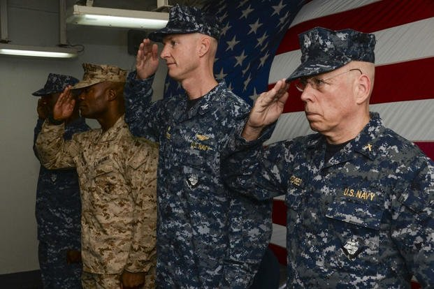 Participants render salutes during the national anthem as part of a change of command ceremony aboard the amphibious assault ship USS Boxer (LHD 4). (Photo: Mass Communication Specialist 3rd Class Michael T. Eckelbecker)