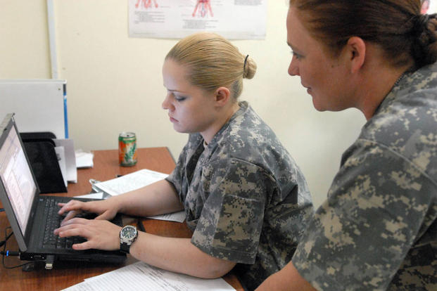 Pfc. Dominka Jakubczak (left), of Yuma, N.M., enters data into a computer system, Sept. 24 2009, after screening patients at the Hale Koa Medical Facility with help from Spc. Anna Hatfield, from Conroe, Texas. (Photo: Pfc. Bailey Jester)