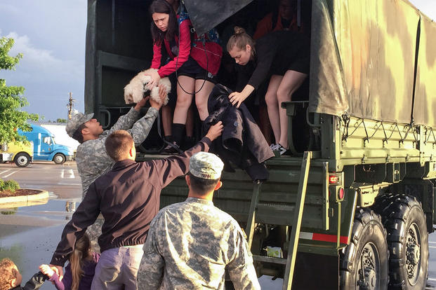 Soldiers help residents out the back of a high-water vehicle after severe flooding in Baton Rouge, La., Aug. 14, 2016. Guardsmen rescued more than 3,400 people and 400 pets since operations began Aug. 12. (Army National Guard photo)
