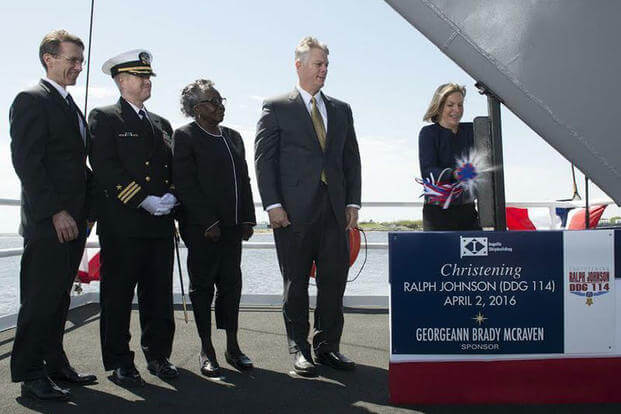 Ship Sponsor Georgeann McRaven breaks a bottle of champagne on the bow during the christening ceremony for the future guided missile destroyer USS Ralph Johnson (DDG 114), April 2, 2016. (U.S. Navy photo courtesy of Huntington Ingalls Industries)