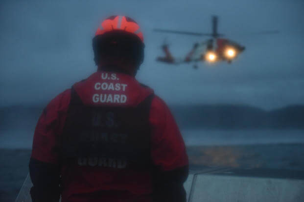 Petty Officer 3rd Class Kevin Walters watches as a Coast Guard Air Station Sitka MH-60 Jayhawk helicopter approaches the ANT's 38-foot aids to navigation boat while underway in Sitka Sound, Alaska, March 3, 2015. (U.S. Coast Guard photo/Grant DeVuyst)