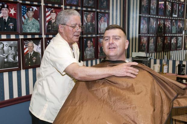 Travis Bell, XVIII Airborne Corps barber, puts on a barber's cape for his next customer as he prepares to give a haircut at the barber shop located in XVIII Airborne Corps headquarters. (Army Photo/ Spc. Paul A. Holston)