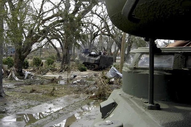 Marines and sailors of a reaction team from Naval Construction Battalion Center ride in amphibious tractors through the ruins of neighborhoods in Southern Mississippi after the devastation of Hurricane Katrina in late August 2005. (Photo By: U.S. Marines)
