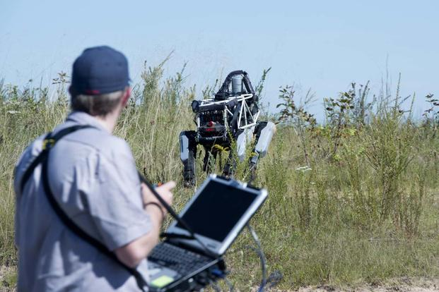 "Ben Swilling, a roboticist from the Defense Advanced Research Projects Agency operates ""Spot"", a quadruped prototype robot, during a demonstration at Marine Corps Base Quantico, Va., Sept. 16, 2015. Photo By: Sgt. Eric Keenan"