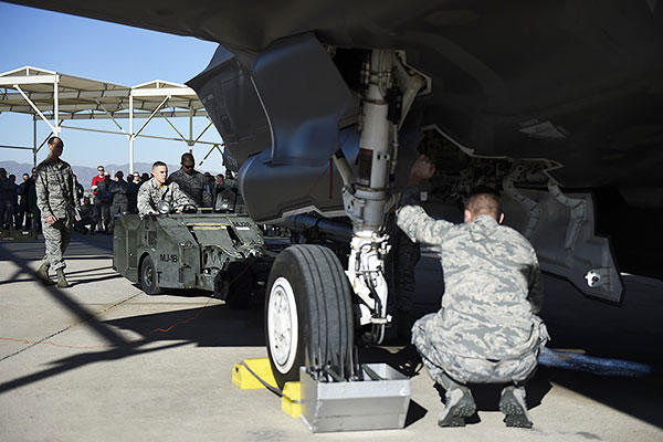 Weapons load crew members from the 61st Aircraft Maintenance Unit load an F-35A Lightning ll during a load crew competition Dec. 18, 2015, at Luke Air Force Base, Ariz. (U.S. Air Force photo/Staff Sgt. Staci Miller)